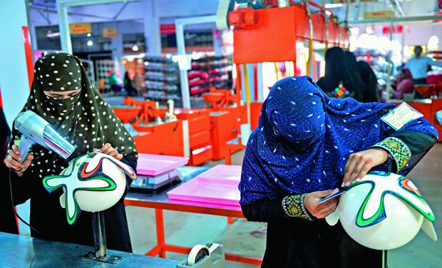 A Pakistani worker prepares the outer covering of footballs at a factory in Sialkot.