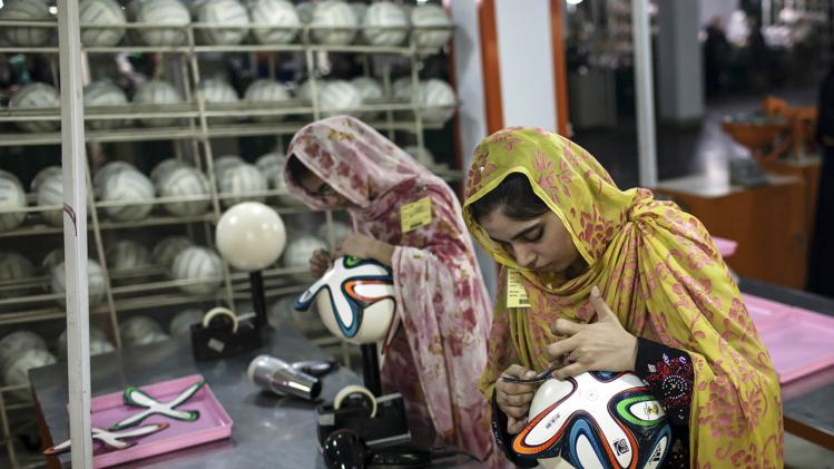 From Sialkot - Pakistan: An employee adjusts outer panels on a soccer ball inside the soccer ball factory that produces official match balls for 2014 World Cup in Brazil