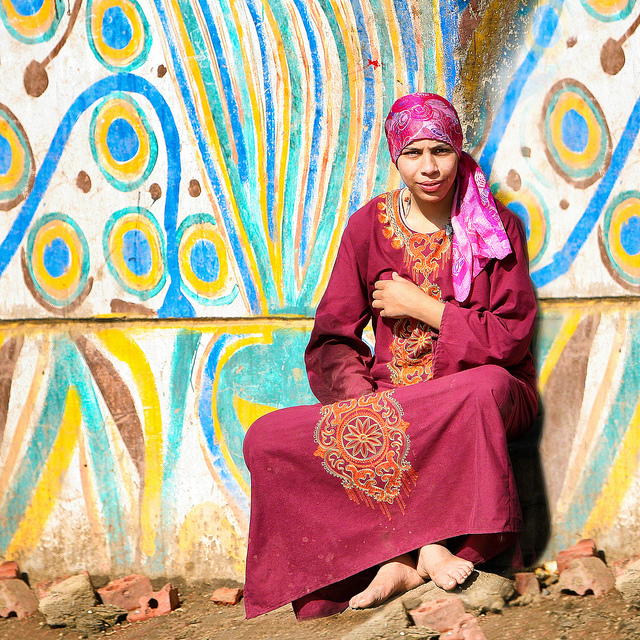 A woman sits outside her house near Memphis, Egypt wearing traditional outfits. Image  by Shawn Clover