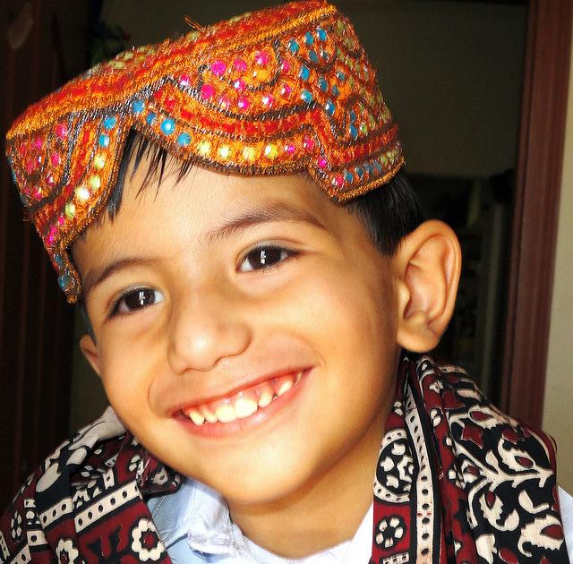 A kid wearing traditional Sindhi cap and Ajrak - Image by tariqkhajar